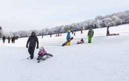 成人和儿童sledding和雪板运动 免版税库存照片