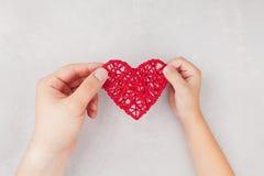 成人和孩子在手上的从上面拿着红色心脏 家庭关系,医疗保健,小儿科心脏病学概念 免版税库存照片