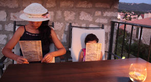 成人和小女孩读取菜单 图库摄影