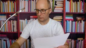 成人商人读书纸张文件在书橱背景的家庭办公室 股票视频