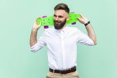 年轻成人商人,拿着在头下他的冰鞋,看起来左和暴牙微笑 浅绿色的背景 免版税库存图片