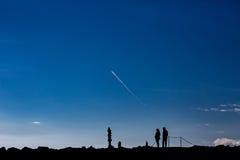 成人夫妇剪影在享用石禅宗堆的天空下 免版税库存图片