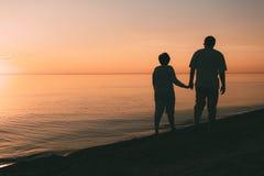 成人夫妇剪影在海滨走反对日落 免版税库存图片
