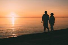 成人夫妇剪影在海滨走反对日落 库存图片