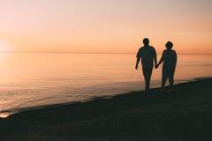 成人夫妇剪影在海滨走反对日落 免版税图库摄影