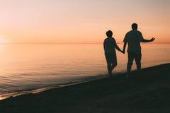 成人夫妇剪影在海滨走反对日落 图库摄影
