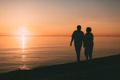 成人夫妇剪影在海滨走反对日落 免版税库存照片