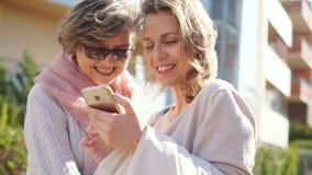 成人女儿和她的中年母亲观看的照片在智能手机身分在街道中间  股票录像