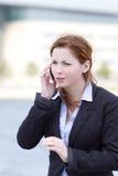年轻成人女商人谈话在巧妙的电话 库存照片