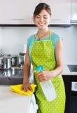 成人女孩打扫灰尘表面在厨房里 库存照片