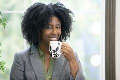 成人学生饮用的咖啡在类面前 免版税库存图片