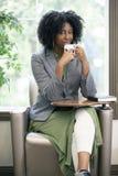 成人学生饮用的咖啡在类面前 图库摄影