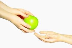 成人孩子给一个苹果 Appple,在白色背景的手上 免版税库存照片