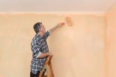 成人工作者油漆墙壁在桔子的一间屋子里 免版税库存图片