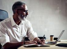 成人成功的商人戴经典眼镜和与膝上型计算机一起使用在木桌上在现代顶楼 博若莱红葡萄酒 免版税库存照片