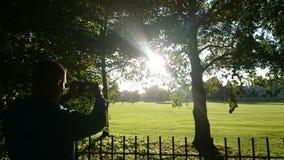 成人拍太阳的照片 免版税库存图片
