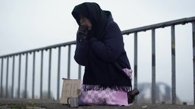 成人无家可归的妇女坐在冷的有风灰色天气的桥梁请求施舍和帮助和咳嗽 股票录像