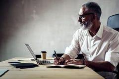 成人时髦的商人戴经典眼镜和与膝上型计算机一起使用在木桌上在现代顶楼 博若莱红葡萄酒 免版税库存图片