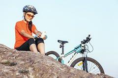 成人有吸引力女性骑自行车者休息室外,看s 免版税库存照片