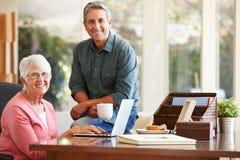 成人有膝上型计算机的儿子帮助的母亲 免版税库存图片