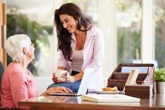 成人有膝上型计算机的女儿帮助的母亲 免版税库存照片