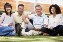 成人校园草坪坐的学员 免版税库存图片