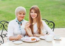成人母亲和女儿饮用的茶或者咖啡。 免版税库存图片