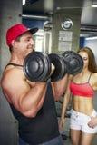 成人爱好健美者摇摆在健身房的二头肌 图库摄影
