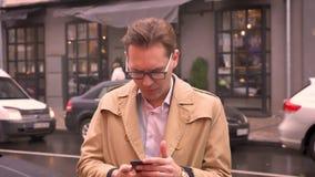成人白种人人采取电话在口袋外面并且得到关于喜讯佩带的外套和站立的通知  影视素材