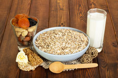 成人的健康饮食:燕麦粥,牛奶,坚果,烘干了在背景黑暗木头的果子 免版税库存照片