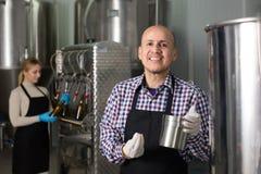 成人笑的男性啤酒厂工作者画象  库存图片