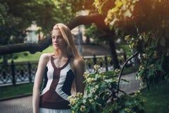 成人美丽的白肤金发的妇女在公园 免版税图库摄影