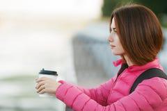 成人美丽的红头发人妇女用在秋天城市河码头的突然移动理发想法的饮用的早晨咖啡 免版税库存照片