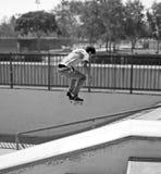 成人耳机踩滑板的年轻人 免版税库存照片