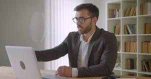 成人英俊的有胡子的白种人商人特写镜头画象在玻璃的有在膝上型计算机的一视频通话在 影视素材