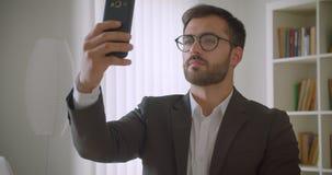 成人英俊的有胡子的白种人商人特写镜头画象在采取在电话的玻璃的selfies在办公室 影视素材