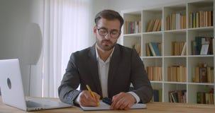 成人英俊的白种人商人特写镜头画象在玻璃的使用采取笔记的膝上型计算机看照相机 股票视频