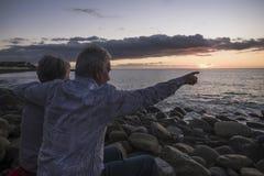 成人资深夫妇的拉丁文的活动在看色的日落的海滩坐海假期和爱概念为 图库摄影