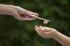 成人递钥匙给孩子 库存图片
