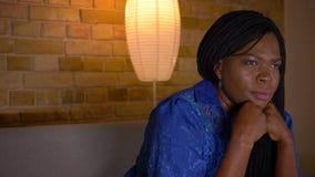 成人非裔美国人的女性看着电视特写镜头射击有被聚焦的好奇表示的坐长沙发户内 股票视频