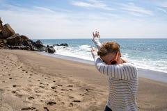 成人caucasion妇女做轻打的舞蹈移动,当在海滩时 采取在点Dume马利布加利福尼亚 免版税库存照片