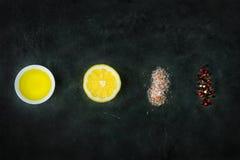 成份平的位置香醋调味汁的 柠檬,橄榄油,喜马拉雅在后面黑板的盐红色黑白胡椒 免版税库存图片