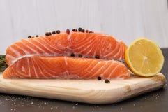成份 柠檬和香料围拢的新鲜的鲑鱼排在一个木板 背景黑色卡片设计花分数维好ogange海报白色 免版税库存照片