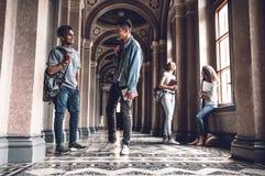 成功和知识在检查帮助我们 站立在大学大厅和聊天的愉快的年轻学生 免版税库存照片
