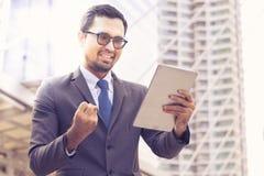 成功商人在网上与数字片剂一起使用,当站立在一个办公室外在城市时 免版税库存图片