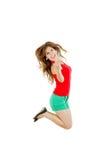 成功女孩跳跃与握紧拳头的喜悦 免版税库存照片