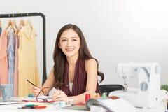 成功年轻女人时尚编辑坐并且微笑着 库存照片