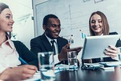 成功微笑的妇女显示某事在计算机片剂染黑商人在业务会议上 免版税库存照片