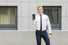成功显示新的巧妙的电话和看照相机的商人 库存图片