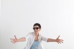 成功正面情感 白色伸前面手的衬衣和太阳镜的愉快的少妇,要拥抱 免版税库存图片